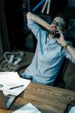 Расслабленный человек говоря на телефоне на столе стоковая фотография rf