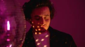Расслабленный человек принимая таблетку экстаза около танцев шарика диско в атмосфере партии клуба сток-видео
