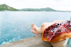 Расслабляющая нога ` s девушки нерезкости на балконе голубого моря Стоковая Фотография RF