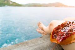 Расслабляющая нога ` s девушки нерезкости на балконе голубого моря Стоковое фото RF