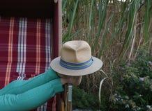 Расслабляющий солнечный день в настелинном крышу плетеном шезлонге также включает Stetson как шляпа солнца стоковые изображения rf