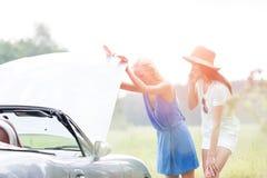 Рассматривать друзей сломанный вниз с автомобиля на солнечный день стоковая фотография rf