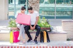 Рассматривая приобретения Соедините сидеть на стенде и держать shopp Стоковое Изображение RF