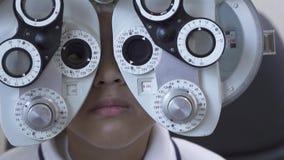 Рассмотрение глаза мальчика на офтальмологе optometrist используя phoropter близкое вверх Милый предназначенный для подростков см видеоматериал