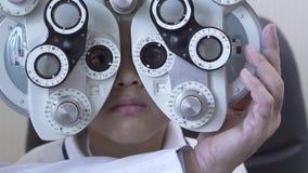 Рассмотрение глаза мальчика на офтальмологе optometrist используя phoropter близкое вверх Рука стекла доктора изменяя видеоматериал