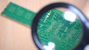 Рассмотрение модуля памяти с лупой компьютер разделяет экспертизу видеоматериал