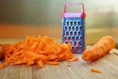 Рассогласование: небольшая терка и большая морковь на разделочной доске стоковое фото