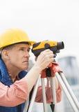 Расстояния рабочий-строителя измеряя через теодолит Стоковое Изображение RF