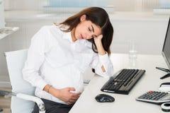 Расстроенная беременная женщина сидя на столе компьютера стоковые изображения rf
