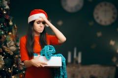 Расстроенная девушка раскрывая плохой подарок рождества находя пижамы внутрь стоковая фотография rf