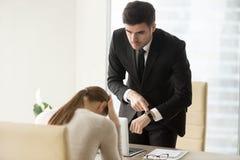 Расстроенная женщина выбраненная боссом для пропущенного крайнего срока, приходя поздно стоковое фото