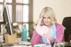 Расстроенная женщина в ее офисе с сердцем валентинки Стоковое фото RF