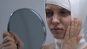 Расстроенная женщина в headwrap смотря отражение зеркала, неудачную хирургию сток-видео