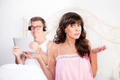 Расстроенная женщина и человек в кровати с таблеткой компьютера Стоковая Фотография
