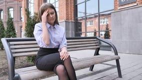 Расстроенная женщина при головная боль сидя офисное здание Ouside на стенде видеоматериал
