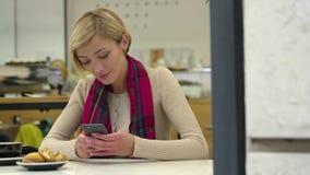 Расстроенная женщина с мобильным телефоном ждать на таблице в кафе видеоматериал
