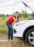 Расстроенная склонность молодой женщины на сломленном автомобиле в поле смотря в камере Стоковое Изображение RF