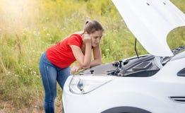 Расстроенная склонность молодой женщины на сломленном автомобиле с открытым клобуком в поле Стоковые Фото