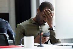Расстроенное молодое африканское сообщение чтения человека на его мобильном телефоне стоковые изображения rf