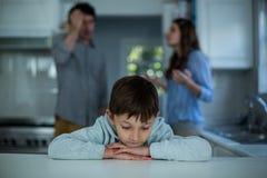 Расстроенное усаживание мальчика пока пары имея аргумент в предпосылке Стоковое Изображение