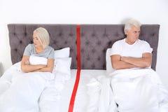 Расстроенные зрелые пары с проблемами отношения лежа отдельно в кровати стоковые изображения