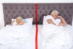 Расстроенные зрелые пары с проблемами отношения лежа отдельно стоковая фотография rf