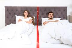 Расстроенные молодые пары с проблемами отношения лежа отдельно в кровати стоковое фото