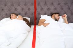 Расстроенные молодые пары с проблемами отношения лежа отдельно в кровати стоковое изображение