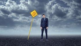 Расстроенный бизнесмен стоя на скалистой земле перед желтым дорожным знаком с нул Стоковое фото RF