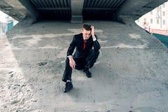 Расстроенный бизнесмен Терпеть неудачу человек Молодой парень в костюме сидит под мостом стоковые изображения rf