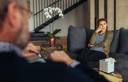 Расстроенный женский пациент во время встречи психотерапии стоковая фотография rf
