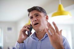 Расстроенный зрелый человек получая продажи вызывает дома стоковые изображения