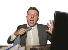Расстроенный и сокрушанный бизнесмен в костюме и связь работая на стрессе стола ноутбука офиса кричащем отчаянном страдая внутри стоковые фото