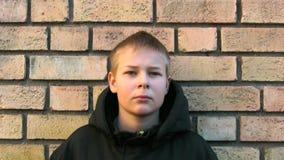 Расстроенный мальчик против стены видеоматериал