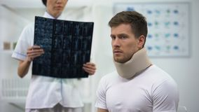 Расстроенный мужчина в воротнике пены цервикальном на рассмотрении, доктор говоря плохой диагноз видеоматериал