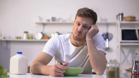 Расстроенный одиночный человек есть безвкусные хлопья на завтрак, недостаток аппетита сток-видео
