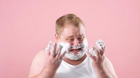Расстроенный пухлый человек в белом undershirt с пеной на бороде, чувствует боль или раздражение, замедленное движение акции видеоматериалы
