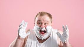 Расстроенный пухлый человек в белом undershirt с пеной на бороде, чувствует боль или раздражение, замедленное движение видеоматериал