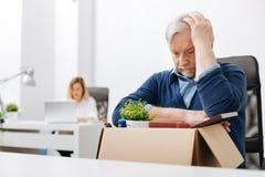 Расстроенный работник офиса собирая пожитки в коробку стоковые фотографии rf