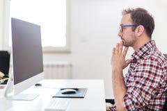 Расстроенный современный предприниматель сидя на столе и смотря мони стоковое фото