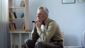 Расстроенный старик полагаясь на идя ручке, принимая ворсину на полдень, чувство сиротливое стоковая фотография rf