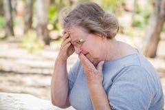 Расстроенный старший сидеть женщины один Outdoors Стоковые Фотографии RF