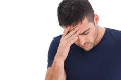 Расстроенный человек стоя при его рука держа его лоб Стоковые Изображения