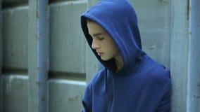 Расстроенный pallid мальчик пряча за загородкой, жертва задирать, несовершеннолетний наркоман лекарства видеоматериал