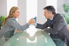 2 расстроенных предпринимателя имея армрестлинг сидя вокруг Стоковое Изображение