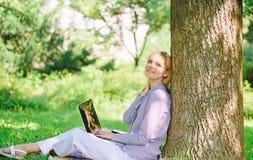 Рассчитайте поминутно для ослабьте Технология образования и концепция интернета Работа девушки с ноутбуком в парке сидеть на трав стоковое фото rf