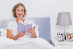 Расслабленная белокурая женщина сидя в кровати держа книгу Стоковые Изображения
