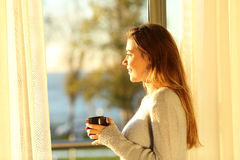 Расслабленная девушка смотря через окно на заходе солнца Стоковые Изображения RF