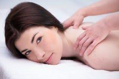 Расслабленная женщина в спа-центре наслаждаясь массажем стоковые изображения rf