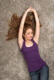 Расслабленная женщина лежа на поле внутри помещения и усмехаться стоковое фото rf